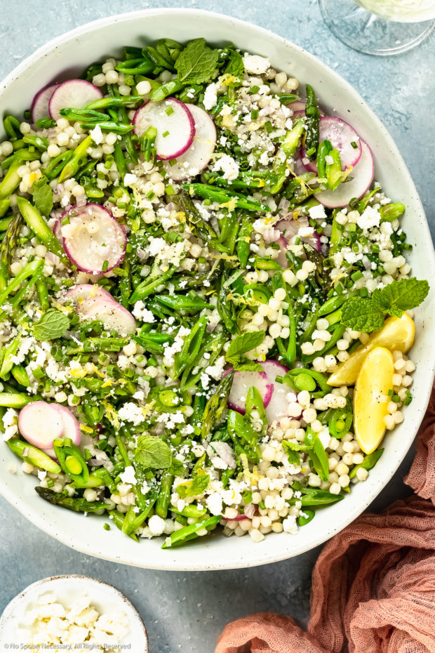 Overhead photo of Lemon Couscous Salad in a neutral colored serving bowl with a ramekin of crumbled ricotta salata, white wine glass and pink linen arranged around the bowl.