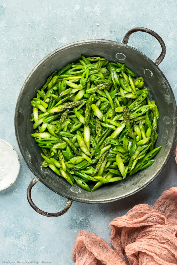 Overhead photo of sautéed sliced asparagus and snap peas seasoned with salt and pepper in a skillet with a ramekin of salt and pink linen arranged around the skillet - photo of step 2 of the lemon couscous salad recipe.