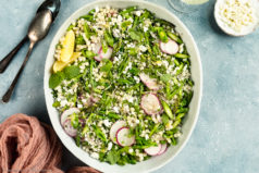 Overhead photo of Lemon Couscous Salad in a neutral colored serving bowl with a ramekin of crumbled ricotta salata, white wine glass, spoons and pink linen arranged around the bowl.