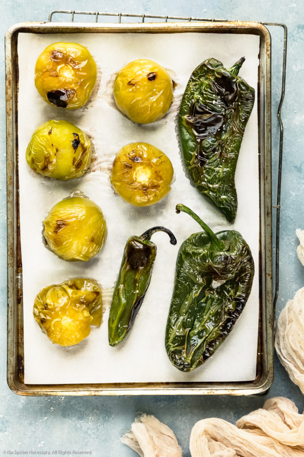 Overhead photo of roasted tomatillos and peppers on a parchment paper lined sheet pan - photo of step 1 of the Homemade Salsa Verde recipe.