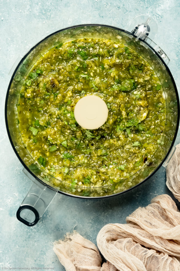 Overhead photo of a food processor bowl filled with processed ingredients for green salsa - photo of step 3 of the recipe.