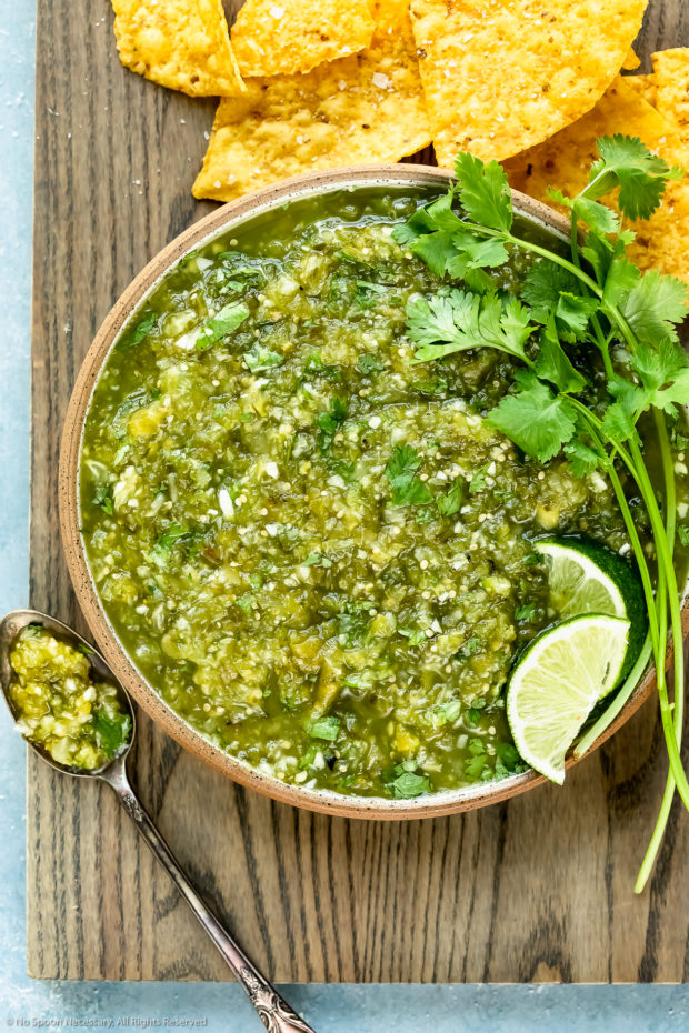 Overhead photo of Homemade Green Salsa topped with lime wedges and fresh cilantro in a neutral colored with a spoon of salsa off to the side and yellow tortilla chips scattered around the bowl.