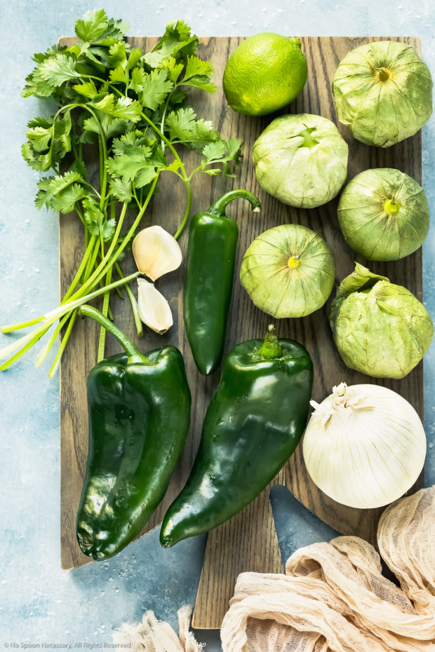 Overhead photo of all the ingredients needed to make Tomatillo Salsa recipe on a gray wood board.