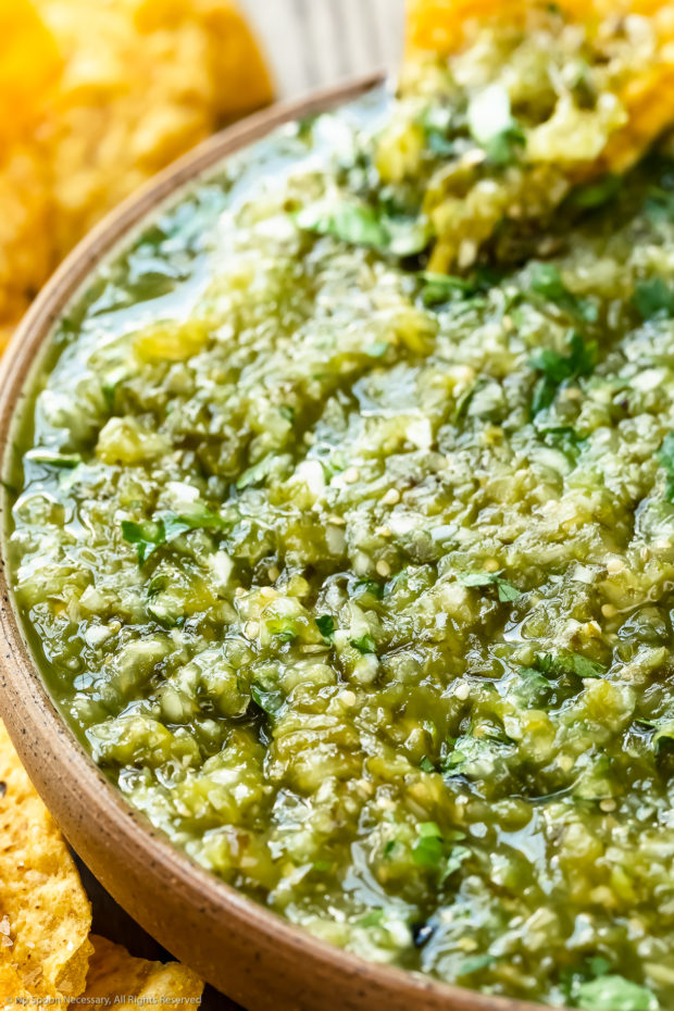 Angled, close-up photo of Green Mexican Salsa in a neutral colored with a yellow tortilla chip dipped into the salsa.