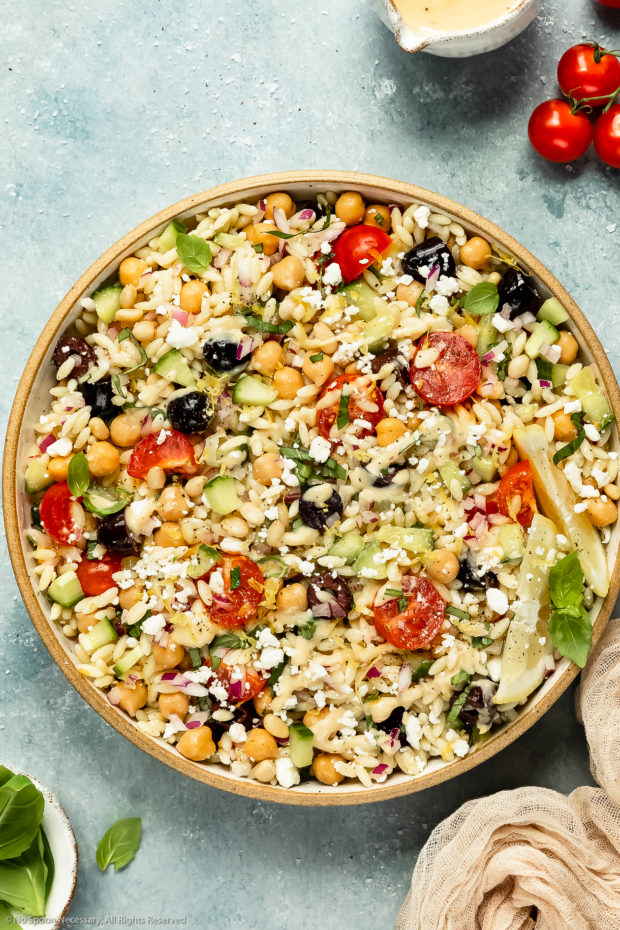 Overhead photo of Greek Orzo Salad drizzled with hummus dressing in a neutral colored bowl with vine-ripe cherry tomatoes and ramekins of dressing and fresh basil arranged around the bowl.