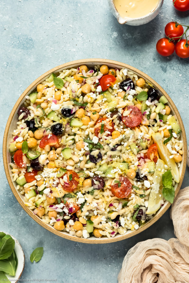 Overhead shot of Greek Orzo Pasta Salad drizzled with hummus dressing in a neutral colored bowl with vine-ripe cherry tomatoes and ramekins of dressing and fresh basil arranged around the bowl.
