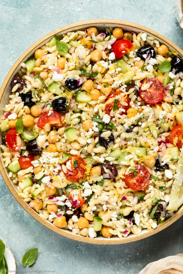 Overhead, close-up photo of Greek Orzo Salad drizzled with hummus dressing in a neutral colored bowl with ramekins of dressing and fresh basil arranged around the bowl.