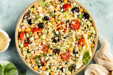 Overhead photo of Greek Orzo Pasta Salad drizzled with hummus dressing in a neutral colored bowl with ramekins of dressing and fresh basil arranged around the bowl.