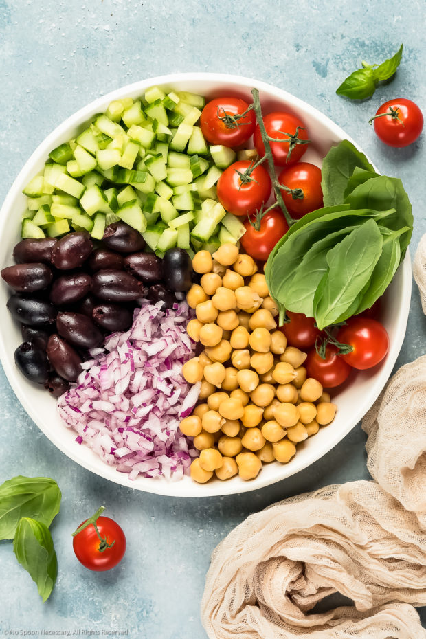 Overhead photo of a large white bowl filled with all the fresh ingredients (tomatoes, cucumbers, olives, red onions, chickpeas and basil) used in Greek Pasta Salad.