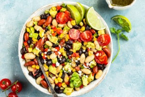 Overhead photo of a Mexican Bean salad with a spoon inserted into the salad in a serving bowl with a small jar of cilantro vinaigrette, vine ripe tomatoes and fresh cilantro arranged around the bowl.