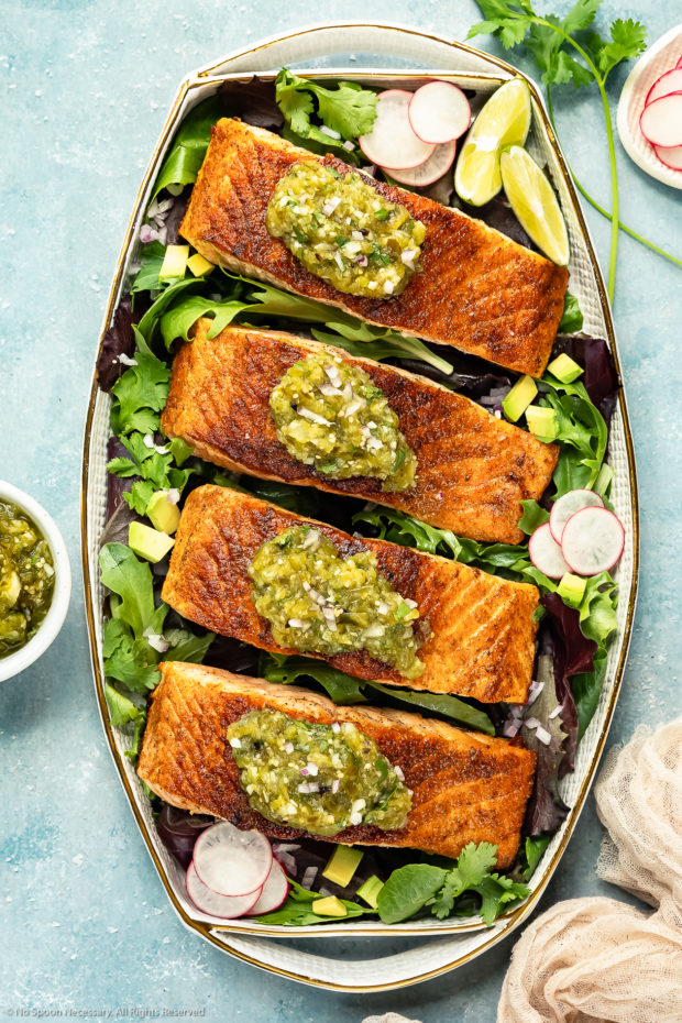 Overhead photo of a white platter topped with pan-seared Salmon garnished with Salsa Verde on a bed of greens with a ramekin of salsa, fresh cilantro and neutral linen arranged around the platter.