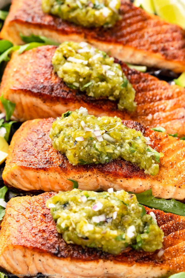 Angled photo of pan-seared Salmon garnished with Salsa Verde on a bed of greens.