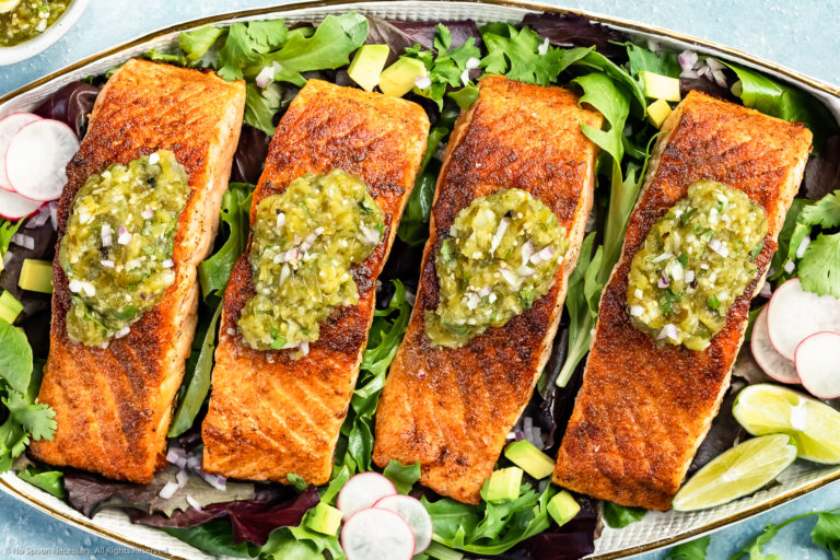 Overhead photo of a white platter topped with pan-seared Salmon garnished with Salsa Verde on a bed of greens.