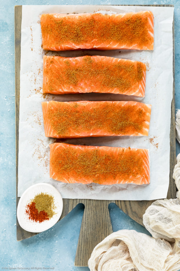 Overhead photo of salmon filets seasoned with paprika and cumin on a parchment paper covered wood board with a ramekin of seasonings next to the salmon - photo of step 1 and 2 of the salmon with salsa recipe.