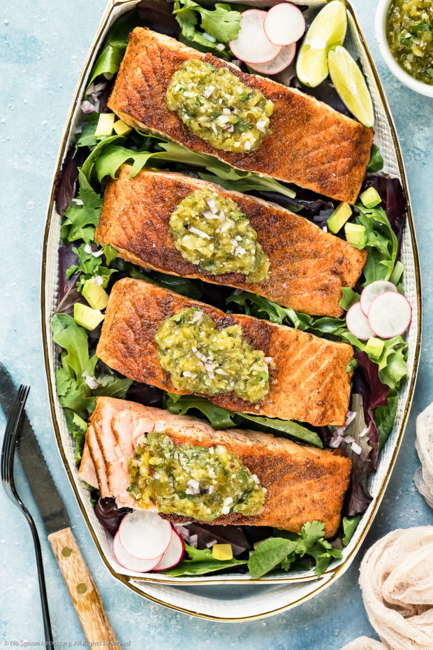 Overhead photo of a white platter topped with pan-seared Salmon garnished with Salsa Verde on a bed of greens with on of the salmon filets cut open to show the inside of the salmon.