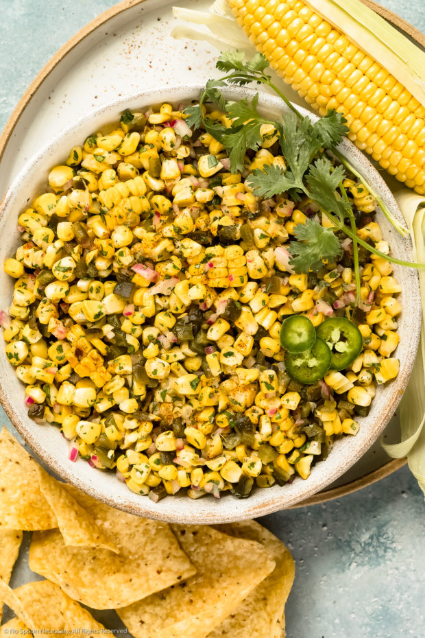 Overhead photo of Sweet Corn Salsa with peppers, onions and cilantro in a large white bowl with an ear of corn and tortilla chips next to the bowl.