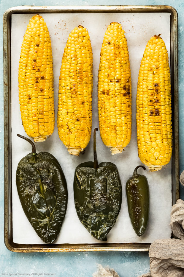 Overhead photo of a parchment paper lined baking pan topped with charred ears of corn and peppers to use in salsa - photo of step 2 of the recipe.