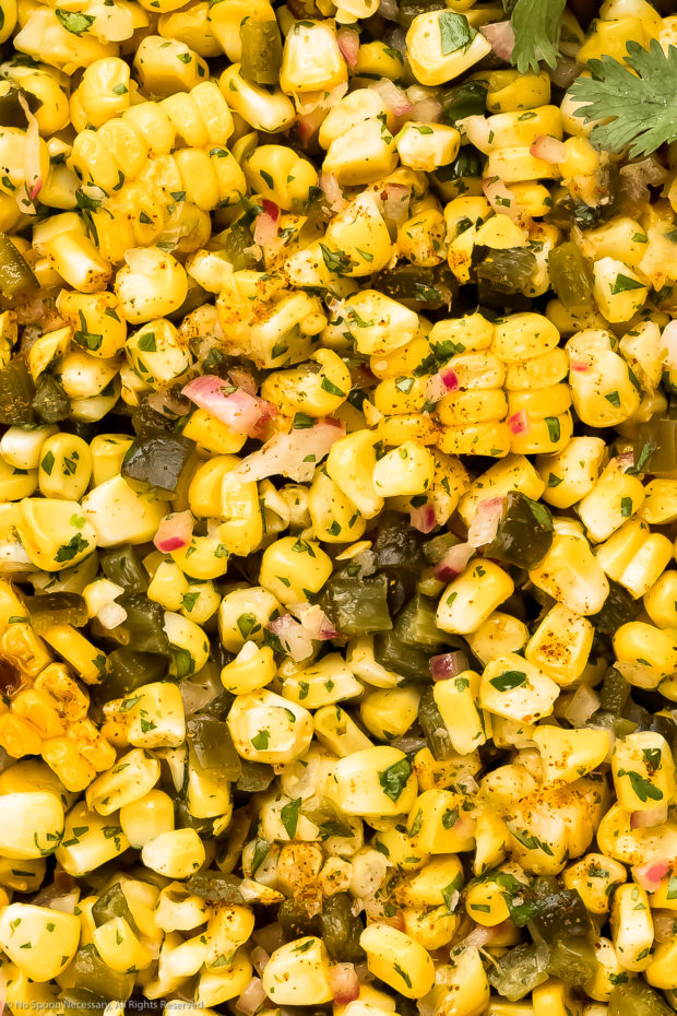 Overhead, extreme close-up photo of homemade corn salsa with peppers and onions.