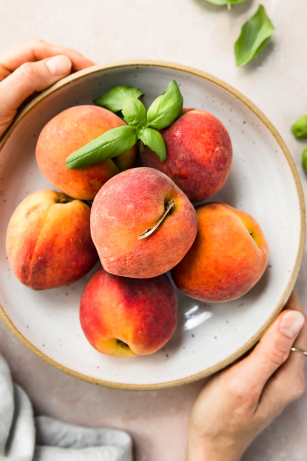 Overhead photo of a white bowl filled with fresh peaches and sprigs of basil with two hands holding the bowl.