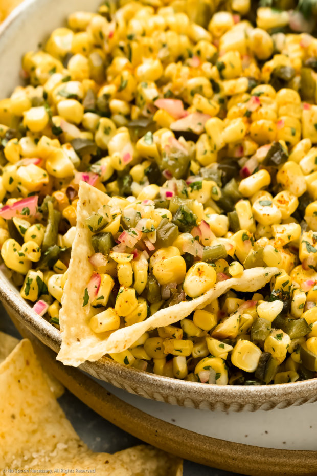 Angled, close-up photo of fresh corn salsa on a tortilla chip in a large serving bowl.