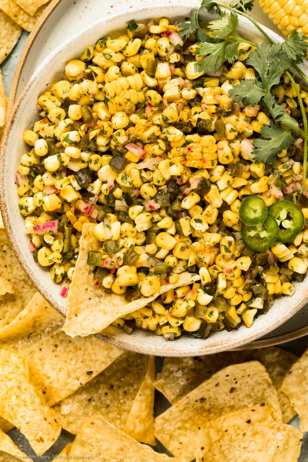 Overhead photo of Sweet and Spicy Corn Salsa a large white bowl with a tortilla chip inserted into the salsa.