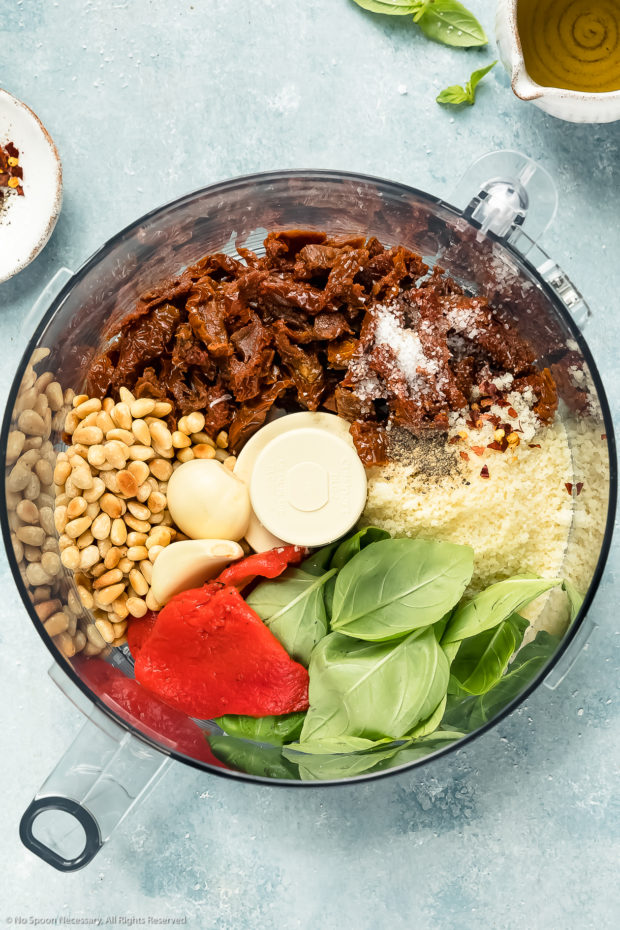 Overhead photo of a food processor bowl filled with sun-dried tomatoes, toasted pine nuts, garlic, red bell pepper, basil leaves, parmesan cheese and seasonings with a ramekin of oil next to the bowl - photo of step 2 of the sun-dried tomato pesto recipe.