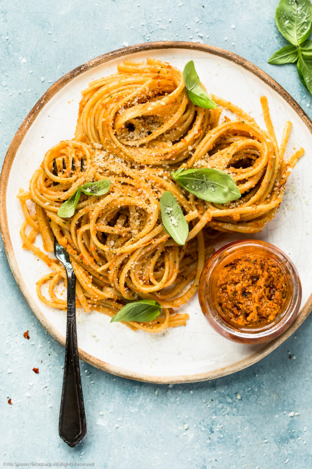 Overhead photo of linguine tossed with sun-dried tomato pesto topped with fresh basil leaves and grated parmesan on a white plate with a jar of pesto next to the pasta - photo of how to use pesto.