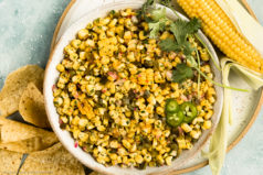 Overhead, landscape photo of Fresh Corn Salsa with peppers, onions and cilantro in a large white bowl with an ear of corn and tortilla chips next to the bowl.