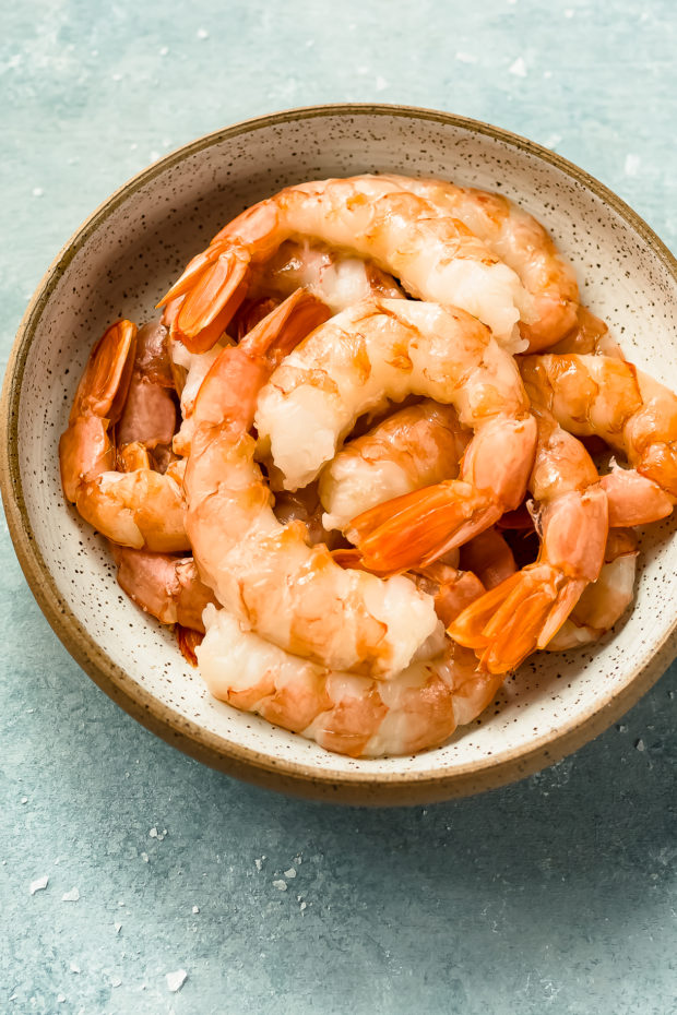Angled photo of peeled and deveined shrimp in a bowl - prep shot for the recipe.