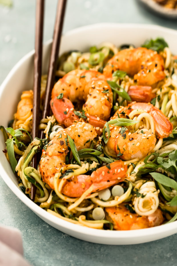 Angled photo of Vegetable Noodle Stir Fry topped with shrimp in a white bowl with a pair of chopsticks inserted into the noodles.