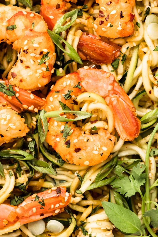 Overhead, close-up photo of stir fry shrimp on top of zucchini vegetable noodles.