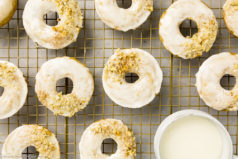 Overhead photo of Baked Apple Cider Donuts on a a gold wire rack with a ramekin of glaze tucked into the corner of the shot.