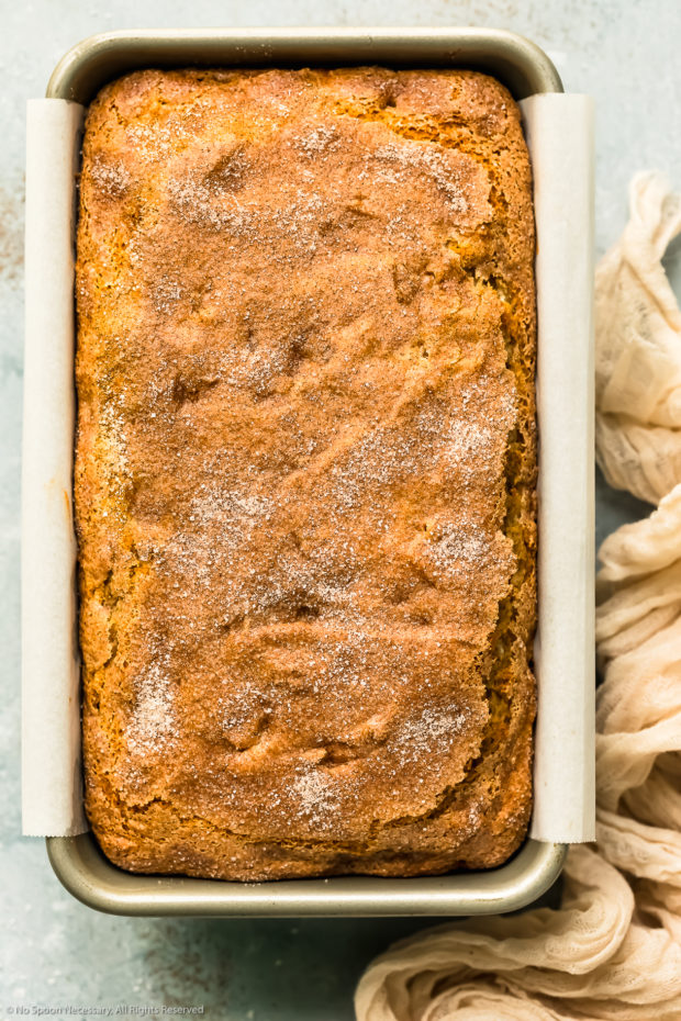 Overhead photo of freshly baked cinnamon apple bread in a parchment paper lined loaf pan - photo of step 9 of the bread recipe.