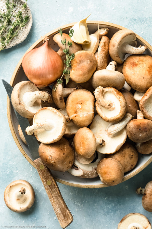 Overhead photo of assorted raw whole mushrooms in a neutral colored bowl with a knife and ramekin of fresh thyme next to the bowl - photo of the main ingredient in easy sauteed mushrooms recipe.