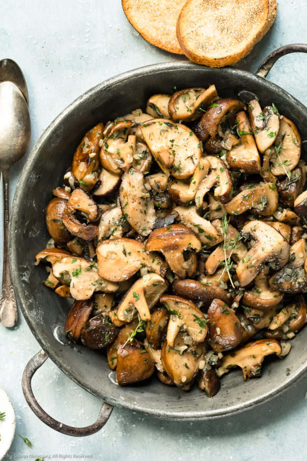 Overhead photo of sauteed mushrooms topped with thyme in a skillet with two pieces of toasted bread and spoons surrounding the skillet.
