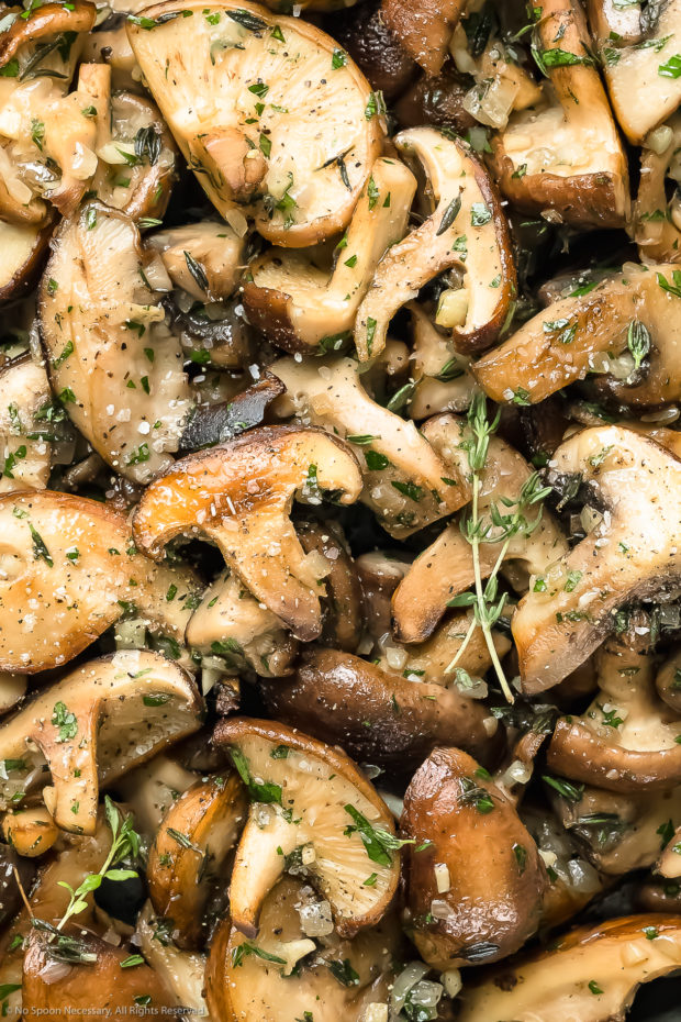 Overhead up close photo of perfectly sauteed mushrooms seasoned with salt, pepper and thyme.