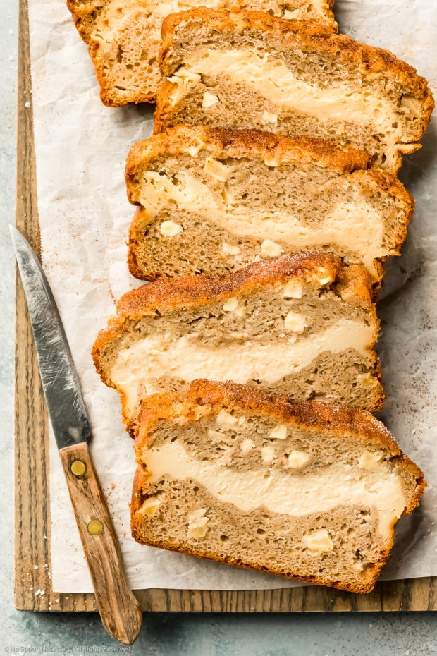 Overhead photo of slices of Fresh Apple Bread with cream cheese filling on a parchment paper lined wood cutting board.