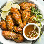 Overhead, landscape photo of Crockpot Asian Chicken Wings garnished with lime wedges and sesame seeds in a parchment paper lined serving bowl with a ramekin of Asian wing sauce next to the wings.