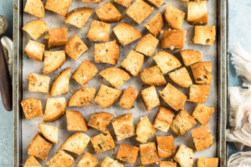 Overhead photo of homemade croutons on a parchment paper lined baking sheet with a ramekin of italian seasoning and neutral colored linen napkin next to the pan.