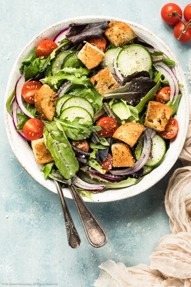 Overhead photo of a simple green salad topped with tomatoes, cucumbers, cucumbers and homemade croutons in a white bowl with a neutral colored linen napkin next to the bowl - photo of how to use easy homemade croutons.