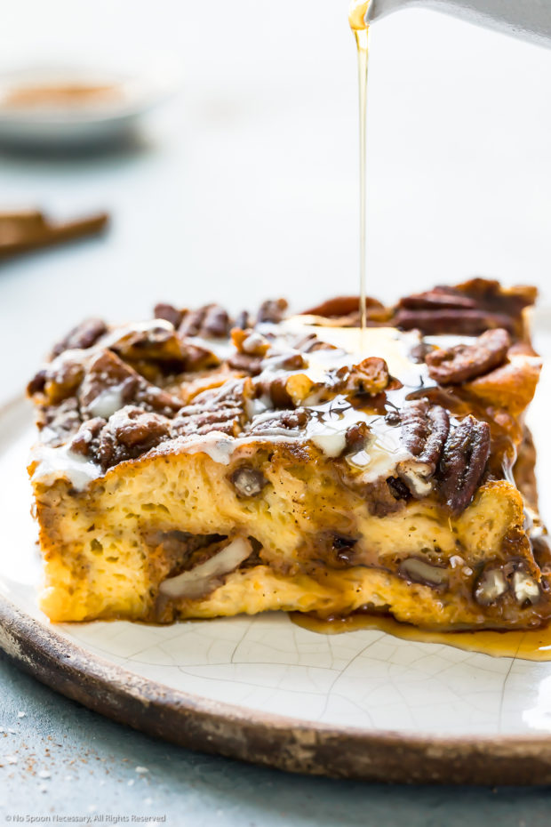 Straight on photo of a slice of Pumpkin French Toast Bake on a white plate with maple syrup being drizzled over the top.