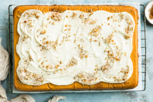 Overhead, landscape photo of Pumpkin Pie Cake topped with swirled maple cream cheese frosting on a wire rack with a ramekin of pumpkin pie spice and a neutral linen next to the cake.
