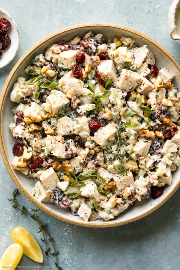 Overhead photo of Cranberry Chicken Salad garnished with sliced scallions and fresh thyme in a serving bowl with lemon wedges, a ramekin of dried cranberries and a jar of dressing next to the bowl.