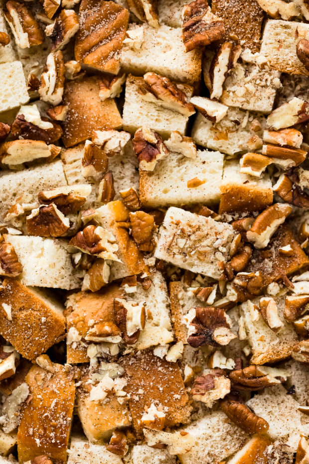 Overhead, close-up photo of cubes of brioche bread sprinkled with cinnamon and chopped pecans - photo of the main ingredients in cinnamon baked French toast.