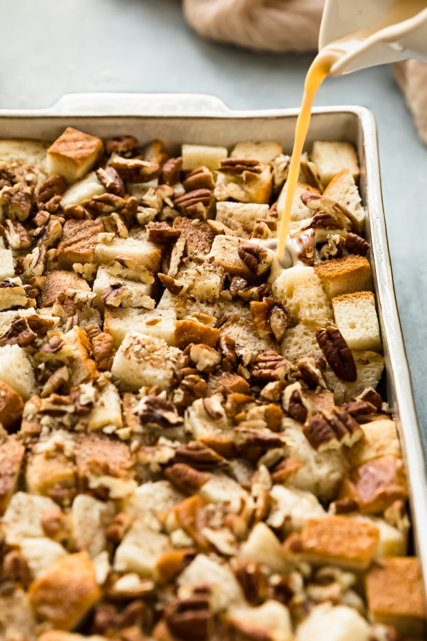 Angled photo of egg custard being poured over cubes of brioche layered with pecans and cinnamon in a white baking dish.