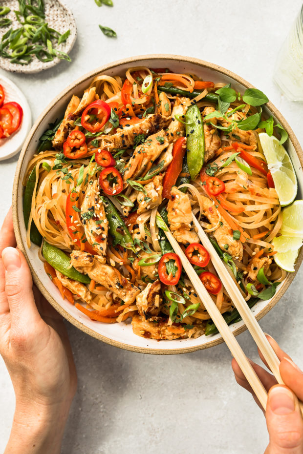 Overhead photo of Chicken with Stir-fry Vegetables in a white bowl with a hand holding a pair of chopsticks inserted into the stir-fry.