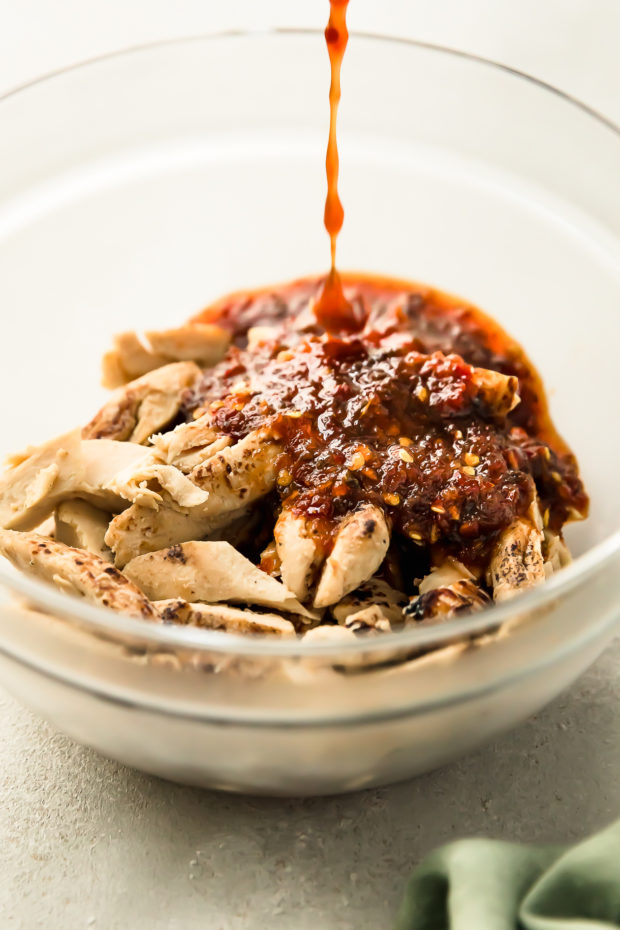 Angled photo of stir-fry sauce being poured onto cooked chicken in a clear bowl - photo of step 1 of the recipe.