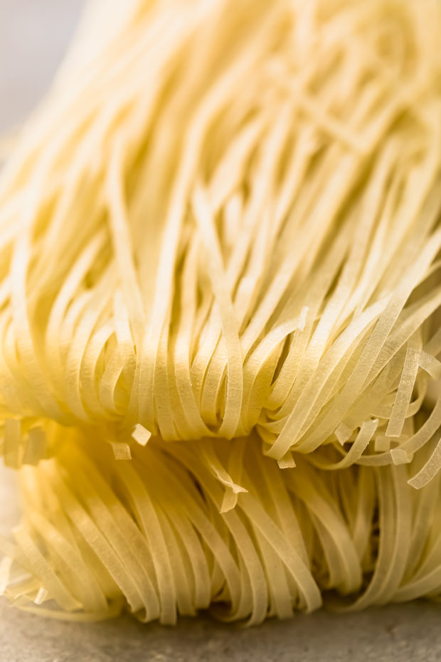 Angled, close-up photo of two stacks of dry Asian rice noodles (photo of one of the main ingredients in the recipe).