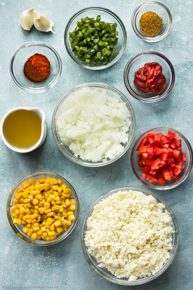 Overhead photo of all the ingredients needed to make Mexican Cauliflower Rice recipe neatly organized into individual glass bowls.