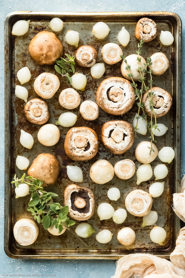 Overhead photo of fresh mushrooms and pearl onions topped with sprigs of fresh herbs on a rimmed baking sheet, before baking.